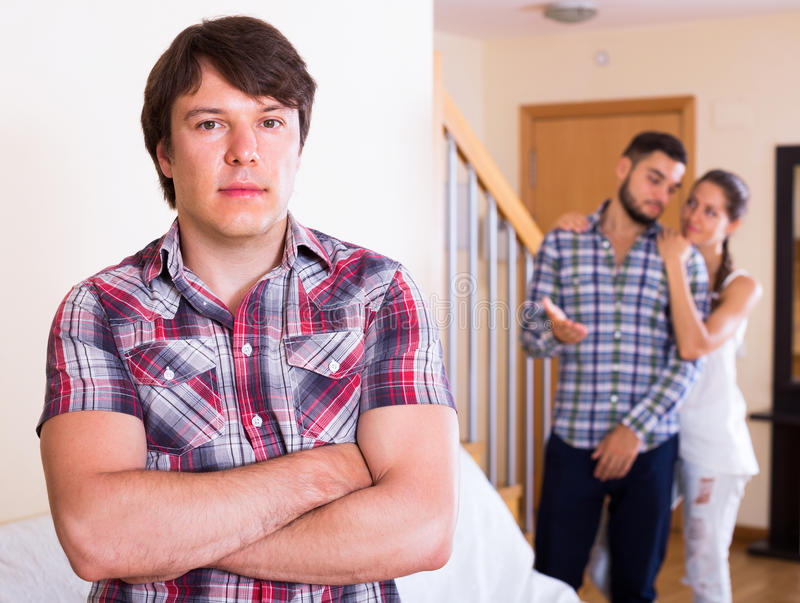Problems of love triangle. Attractive young women and two men: problems of love triangle royalty free stock photo
