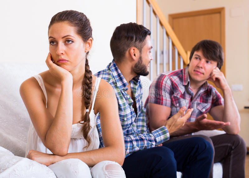 Problems of love triangle. Sad brunette girl and two men at home: problems of love triangle. Selective focus royalty free stock photos