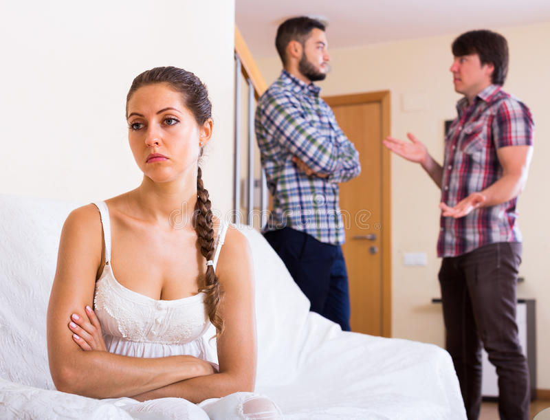 Problems of love triangle. Sad girl and two men at home: problems of love triangle stock photography