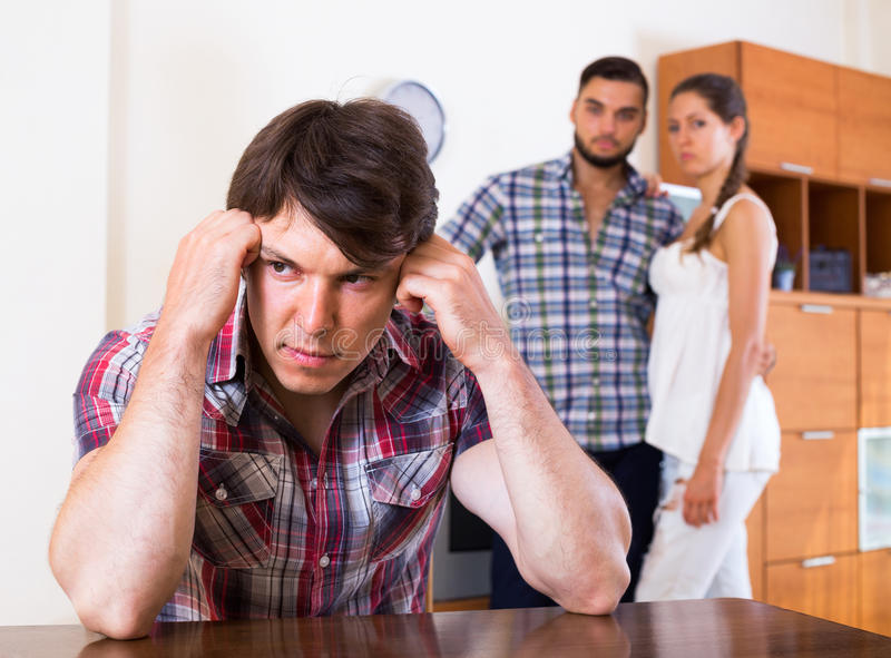 Problems of love triangle. Sad young men and couple at home: problems of love triangle stock images