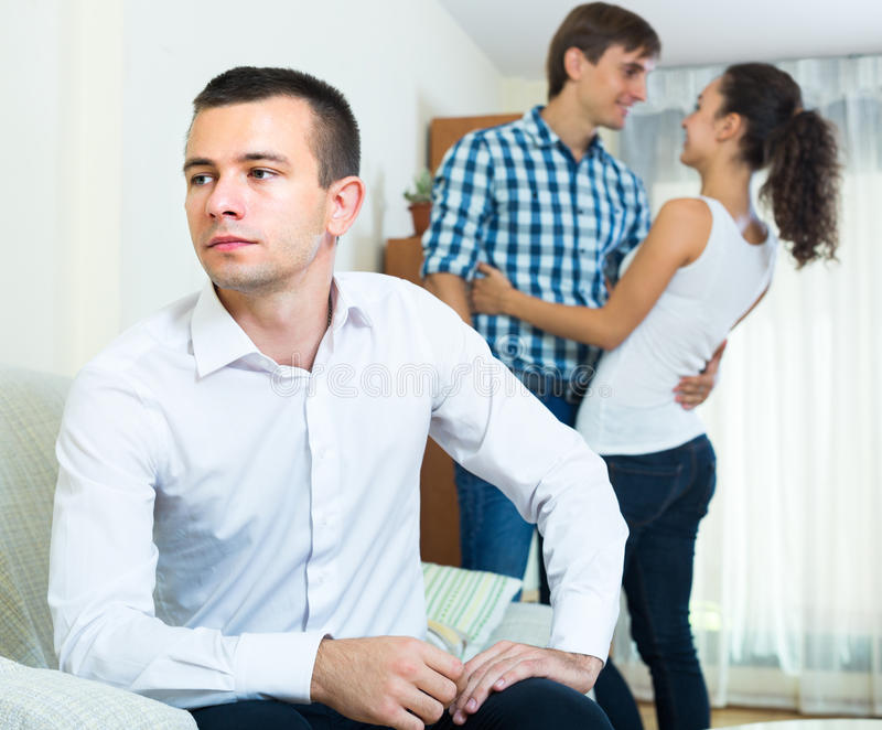Problems of love triangle. Young men suffering in love triangle: young women prefers another guy royalty free stock photo