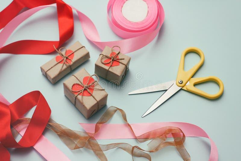 Procédé d'emballage de cadeaux Papier décoratif, rubans en soie, boîte-cadeau, ciseaux Fond bleu-clair images stock