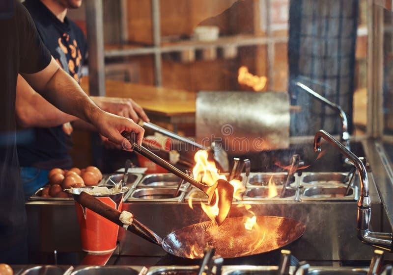 Procédé de cuisson dans un restaurant asiatique Le cuisinier remue des légumes dans un wok sur une flamme images stock