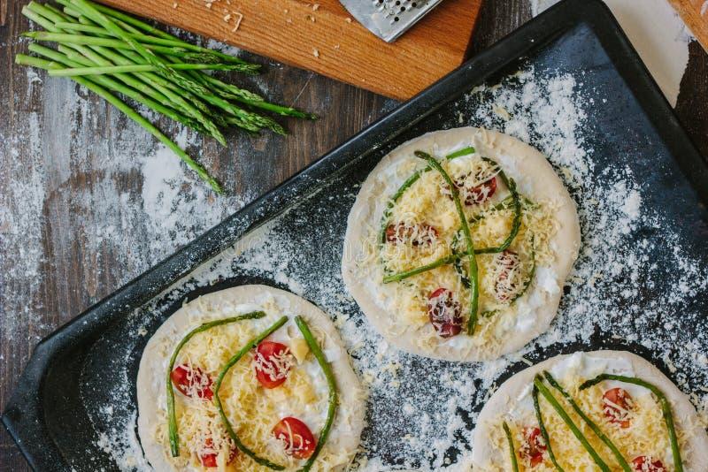 Procédé de cuisson de rendre la mini pizza - petite et personnelle, avec du fromage, les tomates et l'asperge photo stock