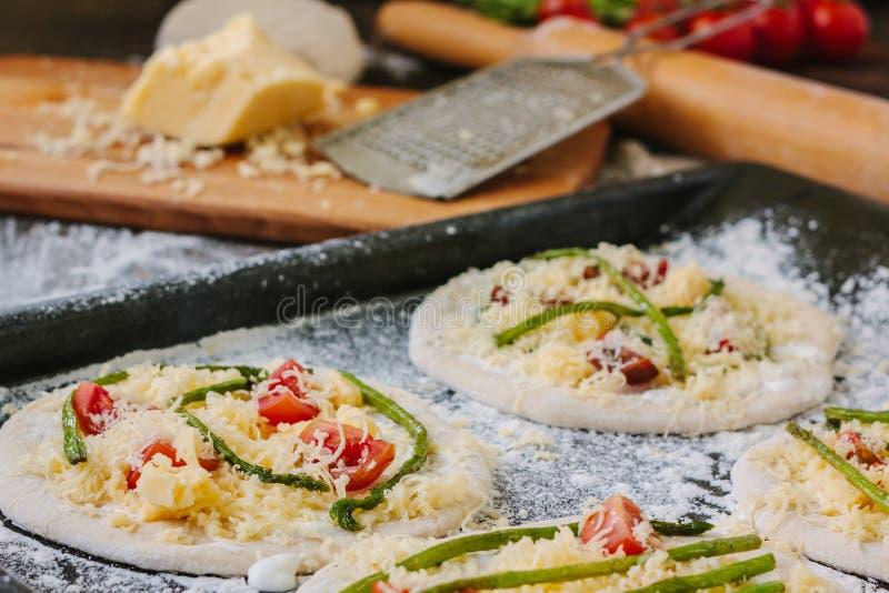 Procédé de cuisson de rendre la mini pizza - petite et personnelle, avec du fromage, les tomates et l'asperge image stock