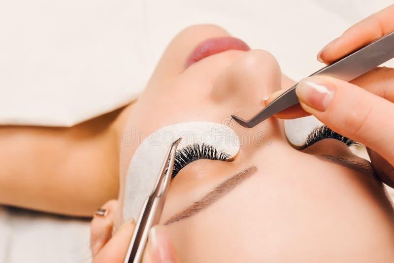 Procédure d'extension de cil Oeil de femme avec de longs cils Fermez-vous vers le haut, foyer sélectif photos stock