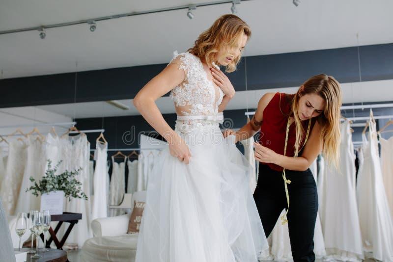 Procedere all'adeguamento all'abito di nozze fotografia stock libera da diritti