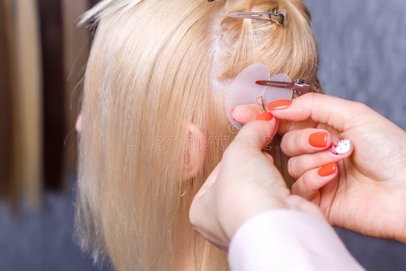Procedimento das extensões do cabelo O cabeleireiro faz extensões do cabelo à moça, louro em um salão de beleza Foco seletivo imagem de stock royalty free