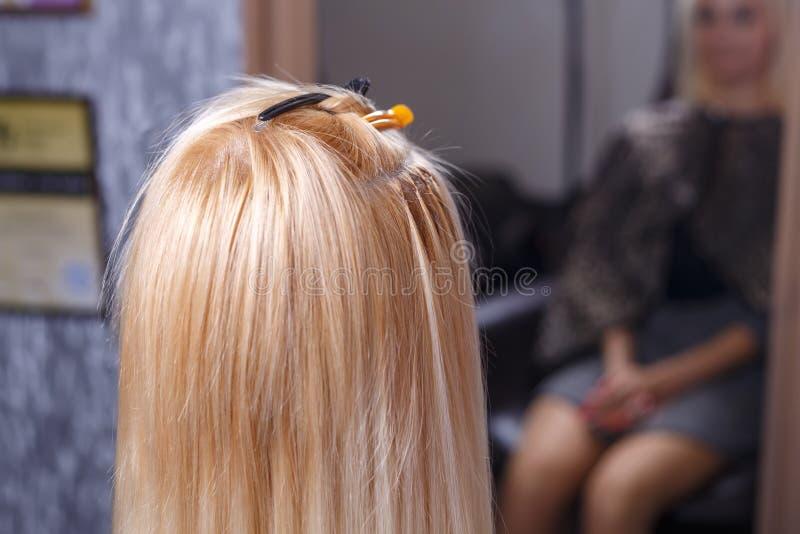 Procedimento das extensões do cabelo O cabeleireiro faz extensões do cabelo à moça, louro em um salão de beleza Foco seletivo foto de stock