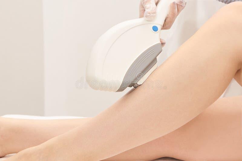 Procedimento médico do cosmeology do laser da beleza Fêmea nova no salão de beleza Doutor profissional Tecnologia do skincare da  imagem de stock royalty free