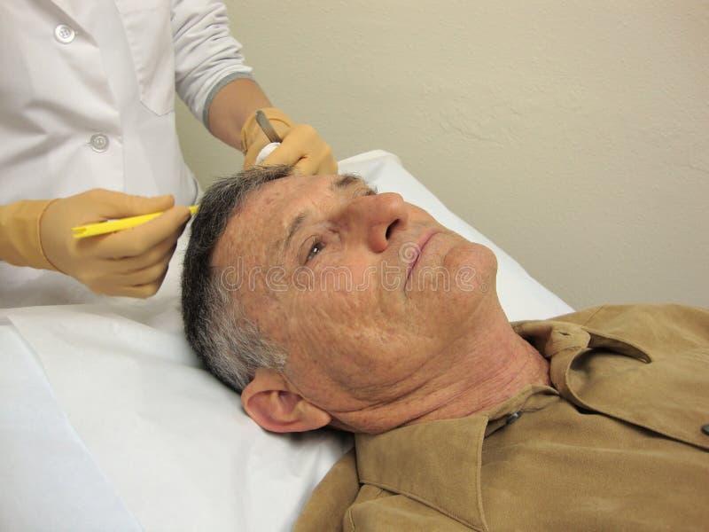 Procedimento médico do doutor Performing imagem de stock royalty free