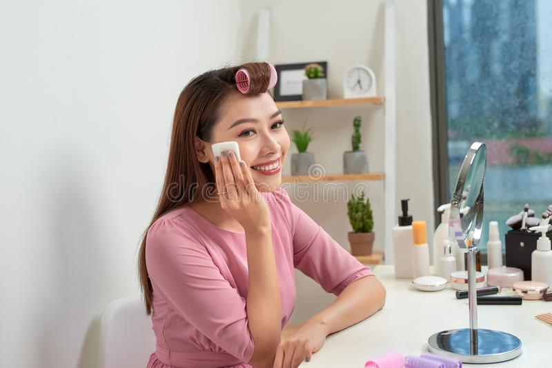 Procedimentos da beleza e conceito cosméticos da reforma Mulher na jovem mulher bonita dos encrespadores de cabelo que usa almofa imagem de stock
