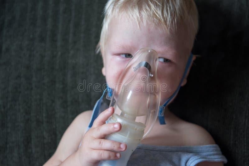 Procedimentos médicos O inalador o louro caucasiano inala os pares que contêm a medicamentação para parar de tossir O conceito do imagens de stock