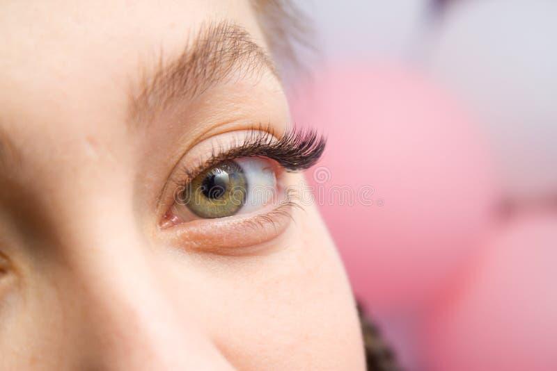 Procedimiento de la extensión de la pestaña Ojo de la mujer con las pestañas falsas largas El cierre encima del tiro macro de la  foto de archivo