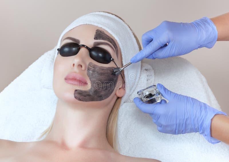 Procedimiento de la peladura de la cara de carbono en un salón de belleza Cosmetología del hardware imagenes de archivo