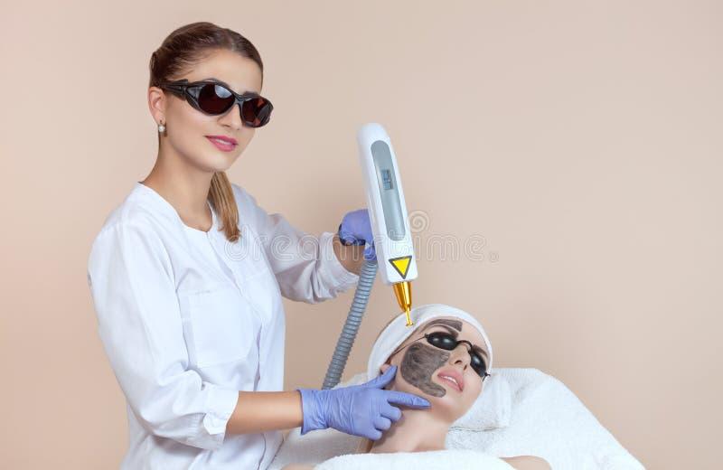 Procedimiento de la peladura de la cara de carbono en un salón de belleza Cosmetología del hardware imagen de archivo