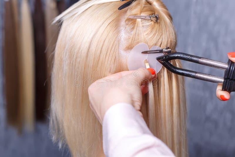Procedimiento de las extensiones del pelo El peluquero hace extensiones del pelo a la chica joven, rubia en un salón de belleza F fotos de archivo