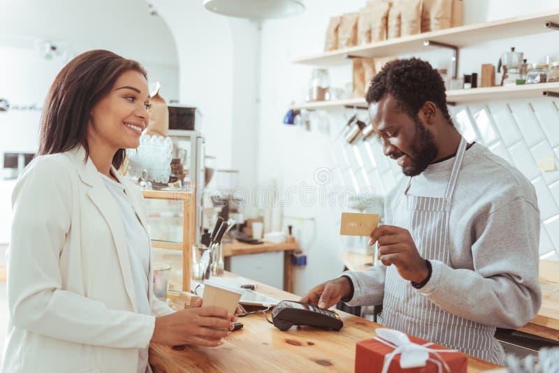 Procedimiento de pago de realización sonriente del barista imagen de archivo libre de regalías