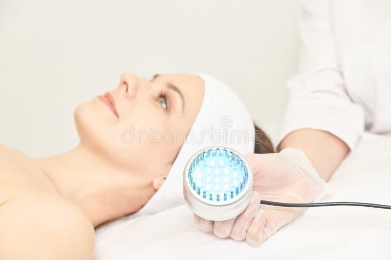 Procedimiento facial de la cosmetolog?a de Skincare Cara de la mujer de la belleza Terapia m?dica ligera azul Mano del especialis fotografía de archivo