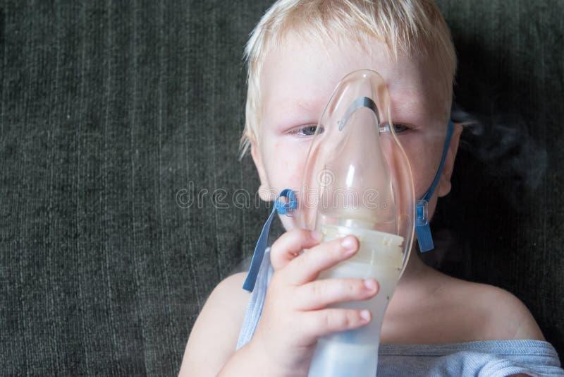 Procedimientos médicos inhalador El blonde caucásico inhala los pares que contienen la medicación para parar el toser El concepto foto de archivo