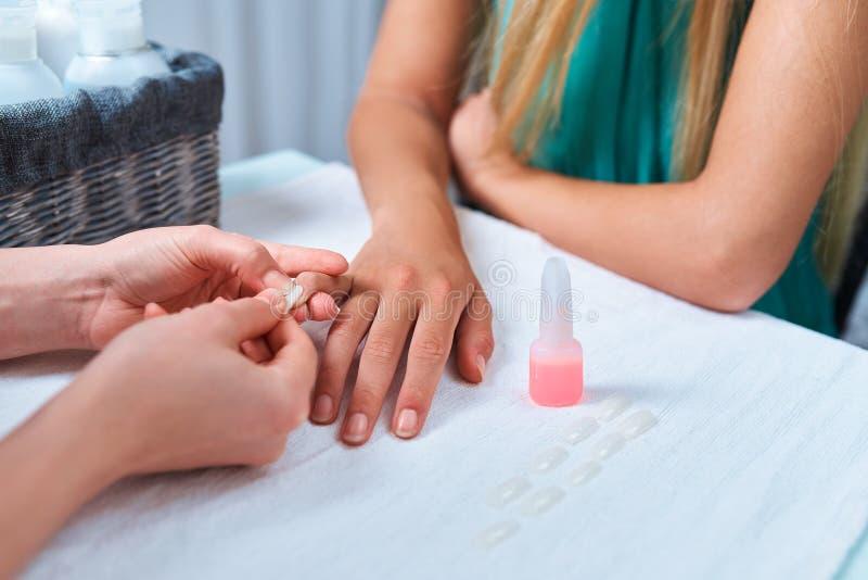 Procedura che incolla i chiodi artificiali unghia dei bastoni del manicure sul cliente del dito immagine stock libera da diritti