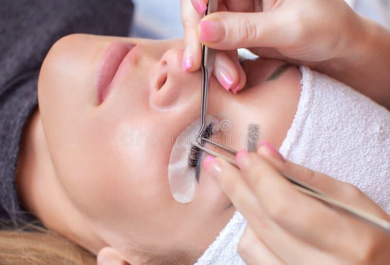 Procedura di estensione del ciglio Bella donna con le sferze lunghe in un salone di bellezza immagine stock libera da diritti