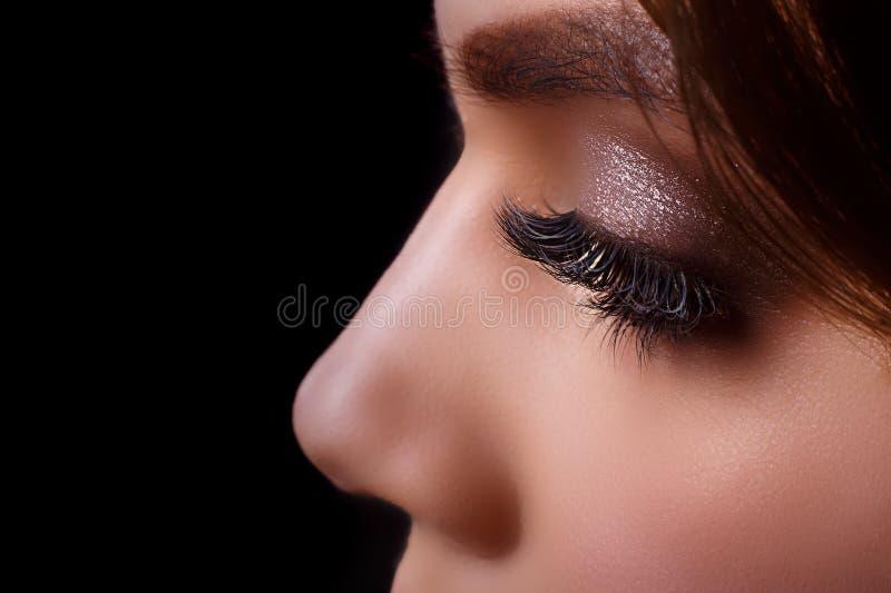 Procedura di estensione del ciglio Occhio della donna con i cigli lunghi dopo la procedura di estensione Cigli bianchi Fondo scur fotografia stock
