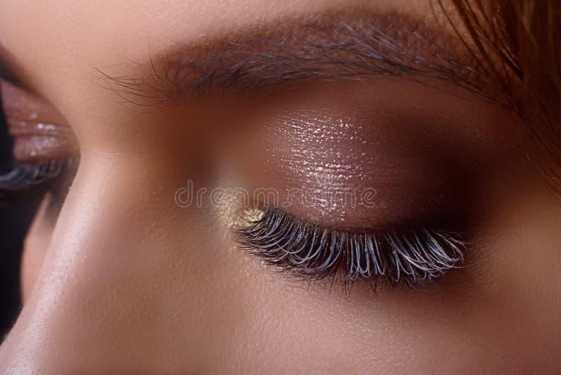 Procedura di estensione del ciglio Occhio della donna con i cigli lunghi dopo la procedura di estensione Cigli bianchi Fondo scur immagini stock