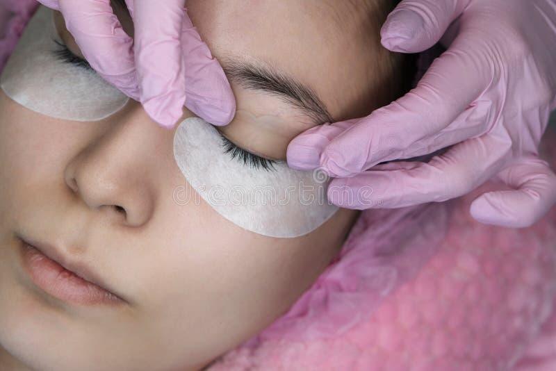 Procedura di estensione del ciglio Occhio della donna con i cigli lunghi fotografie stock libere da diritti