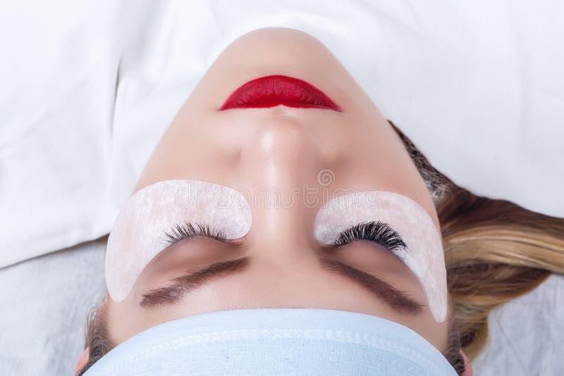 Procedura di estensione del ciglio Occhio della donna con i cigli lunghi Sferze, fine su, fuoco selezionato fotografie stock libere da diritti