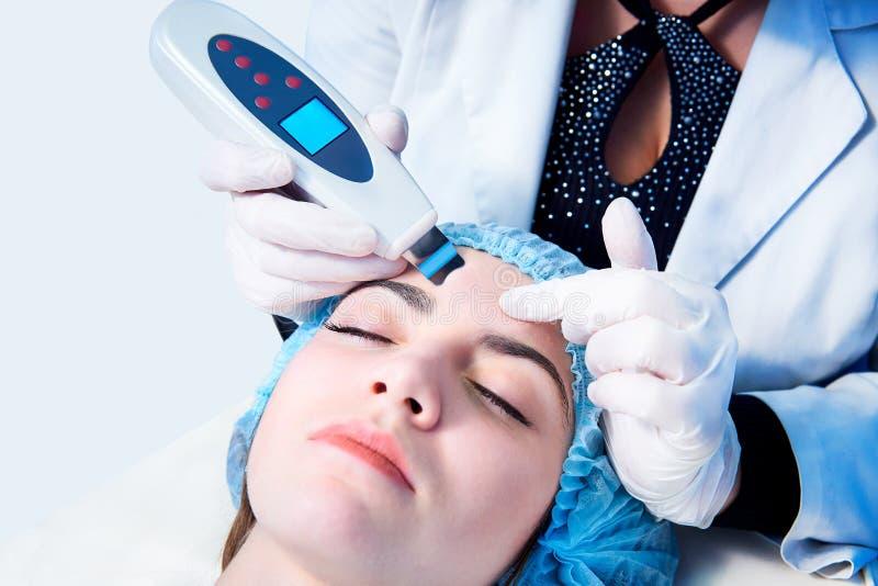 Procedura di pulizia ultrasonica del fronte Trattamento medico e cura di pelle Il medico-cosmetologo rende all'apparato una proce fotografie stock