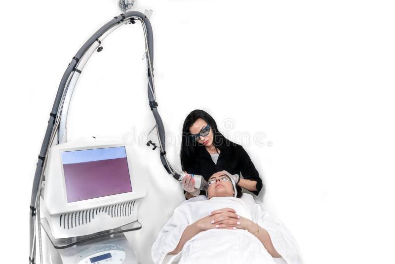 Procedura di trattamento di ringiovanimento della pelle del laser con attrezzatura tecnologica in una stazione termale medica Fon fotografia stock libera da diritti