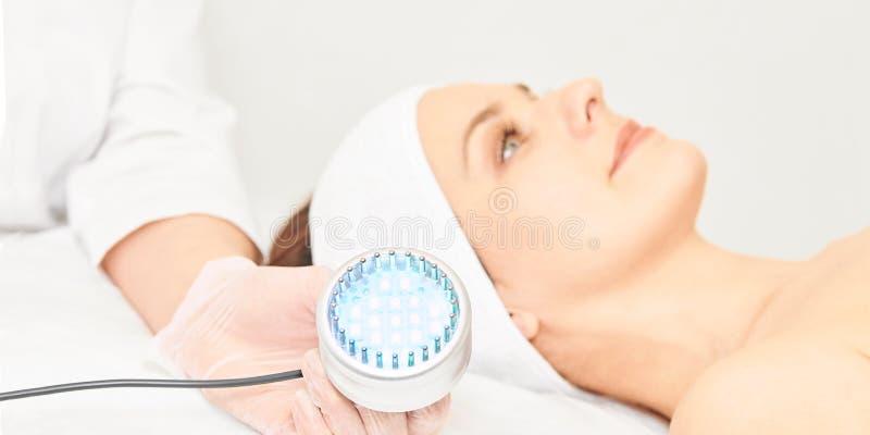 Procedura facciale di cosmetologia di Skincare Fronte della donna di bellezza Terapia medica leggera blu Mano dello specialista immagini stock