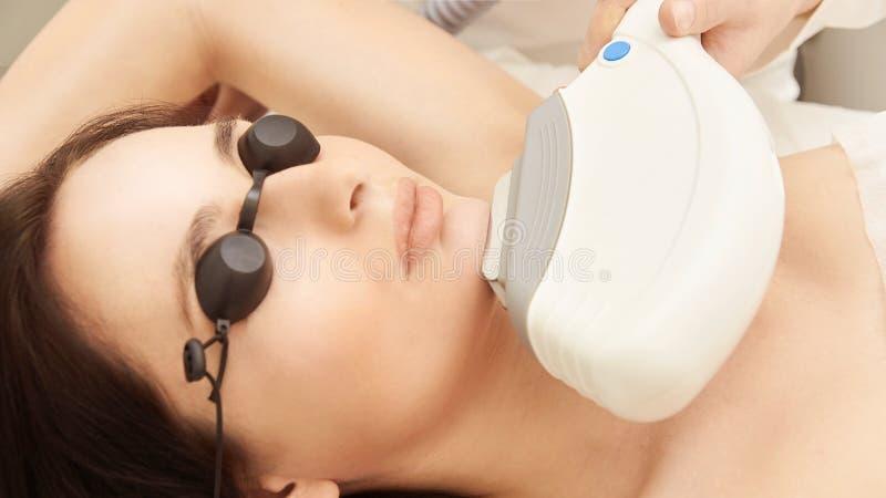 Procedura medica di cosmeology del laser di bellezza Giovane femmina al salone Medico professionista Tecnologia dello skincare de fotografia stock