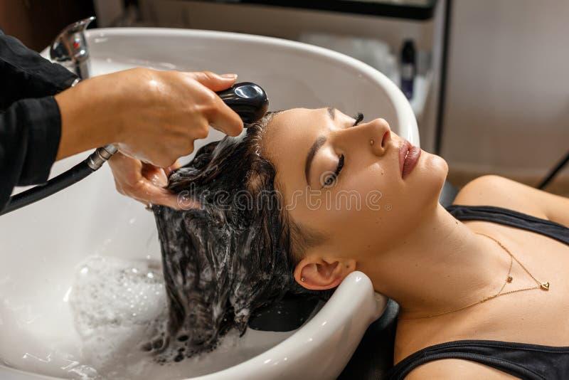 Procedura Mujer joven hermosa con la cabeza que se lava del peluquero en el salón de pelo fotografía de archivo libre de regalías