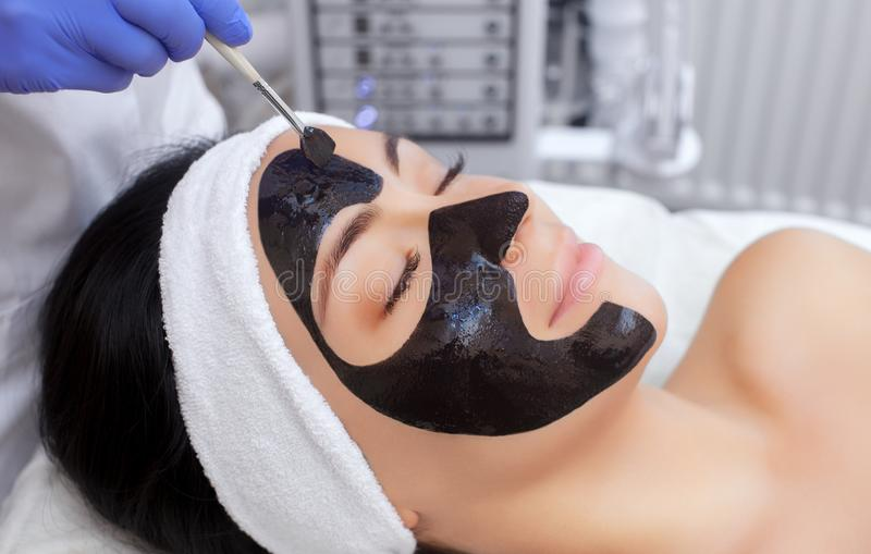 The procedure for applying a black mask to the face of a beautiful woman royalty free stock photos