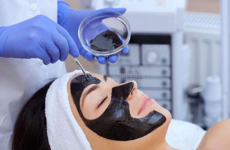 The procedure for applying a black mask to the face of a beautiful woman. royalty free stock image