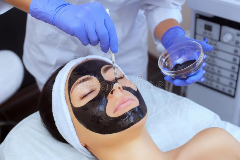 The procedure for applying a black mask to the face of a beautiful woman. Spa treatments and care of the cats in the beauty salon royalty free stock photos