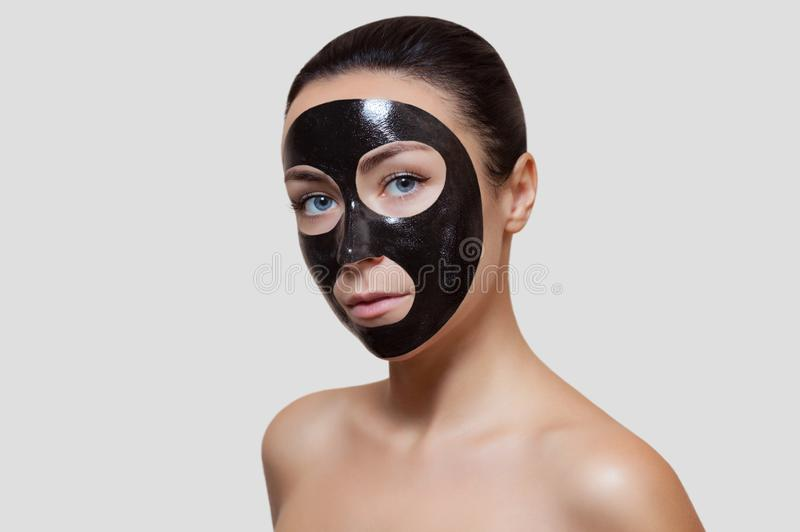 The procedure for applying a black mask to the face of a beautiful woman. stock image