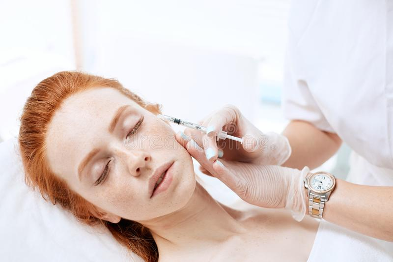 Caucasian red-haired woman gets beauty facial injections. Face aging injection. royalty free stock photography