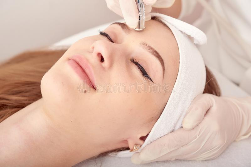 The cosmetologist makes the procedure Microdermabrasion of the facial skin of a beautiful, young woman in a beauty salon royalty free stock images