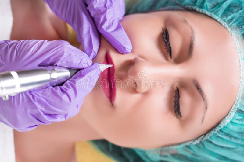 Procedure of professional apply permanent make up in beauty salon on woman lips royalty free stock image