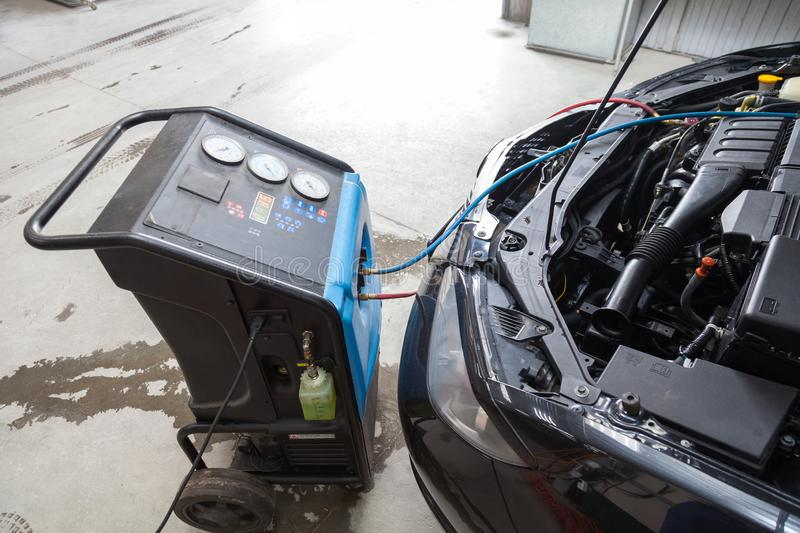 Procedure for refueling a car air conditioner using a special device with a blue compressor and a red hose near the open hood. The procedure for refueling a car stock photo