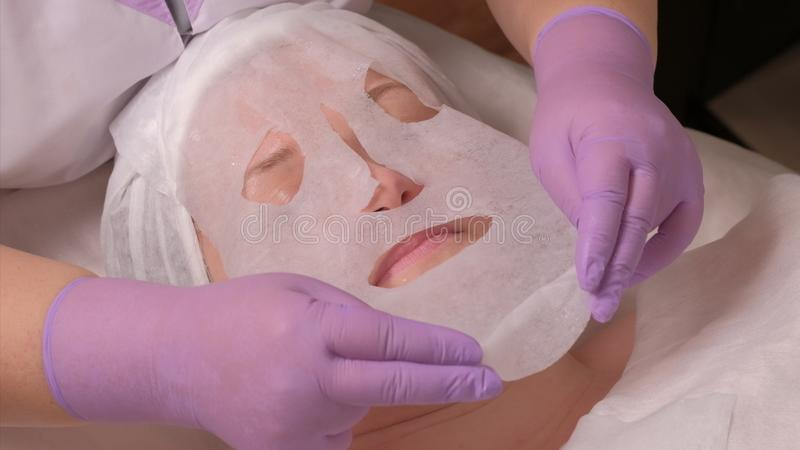 Beauty spa and cosmetology. A professional cosmetologist in lilac gloves puts a mask on a middle-aged woman`s face. The procedure. The procedure of skin stock photos