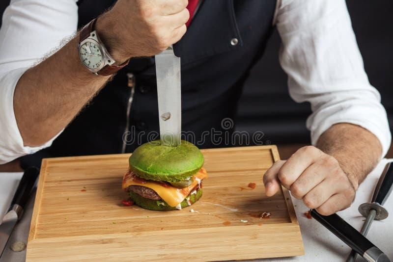 Proces łasowanie hamburgery Mistrzowski Kucbarski tnący smakowity hamburger z szpinak babeczką obrazy royalty free