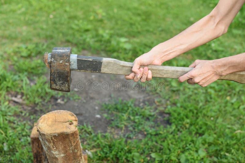 Proces ci?? drewno z cleaver Mężczyzna trzyma cioskę i wokoło siekać obraz royalty free