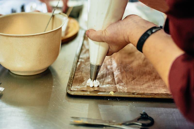 Proces om de industrie van het het dessertvoedsel van schuimgebakjepavlova, massa of volumeproductie te maken gebakjechef-kok die royalty-vrije stock afbeeldingen
