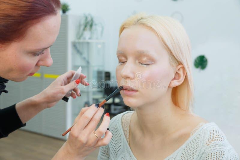 Proces om make-up te maken Grimeur die met borstel aan modelgezicht werken stock foto