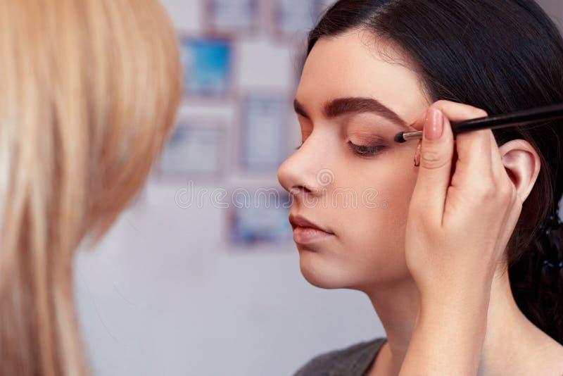 Proces om make-up te maken Grimeur die met borstel aan modelgezicht werken Portret van jonge vrouw in het binnenland van de schoo royalty-vrije stock fotografie