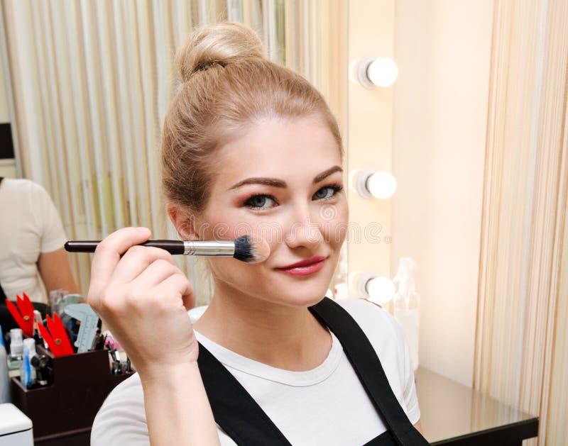 Proces om make-up te maken Mooie jonge vrouw die toon toepassen op huid Hand met borstel op modelgezicht royalty-vrije stock foto